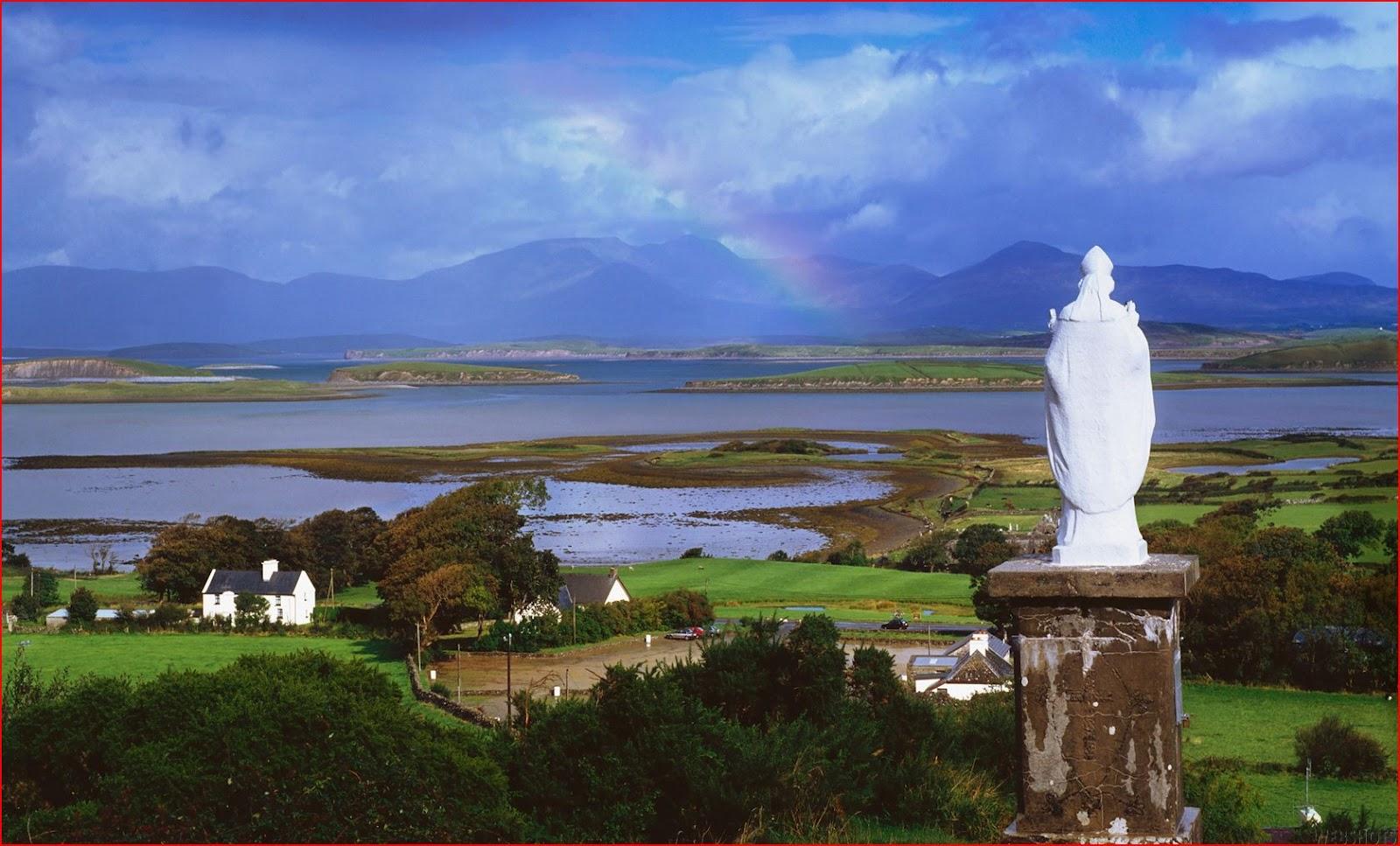 Una statua di San Patrizio rivolta verso le verdi distese irlandesi (Mayo County).