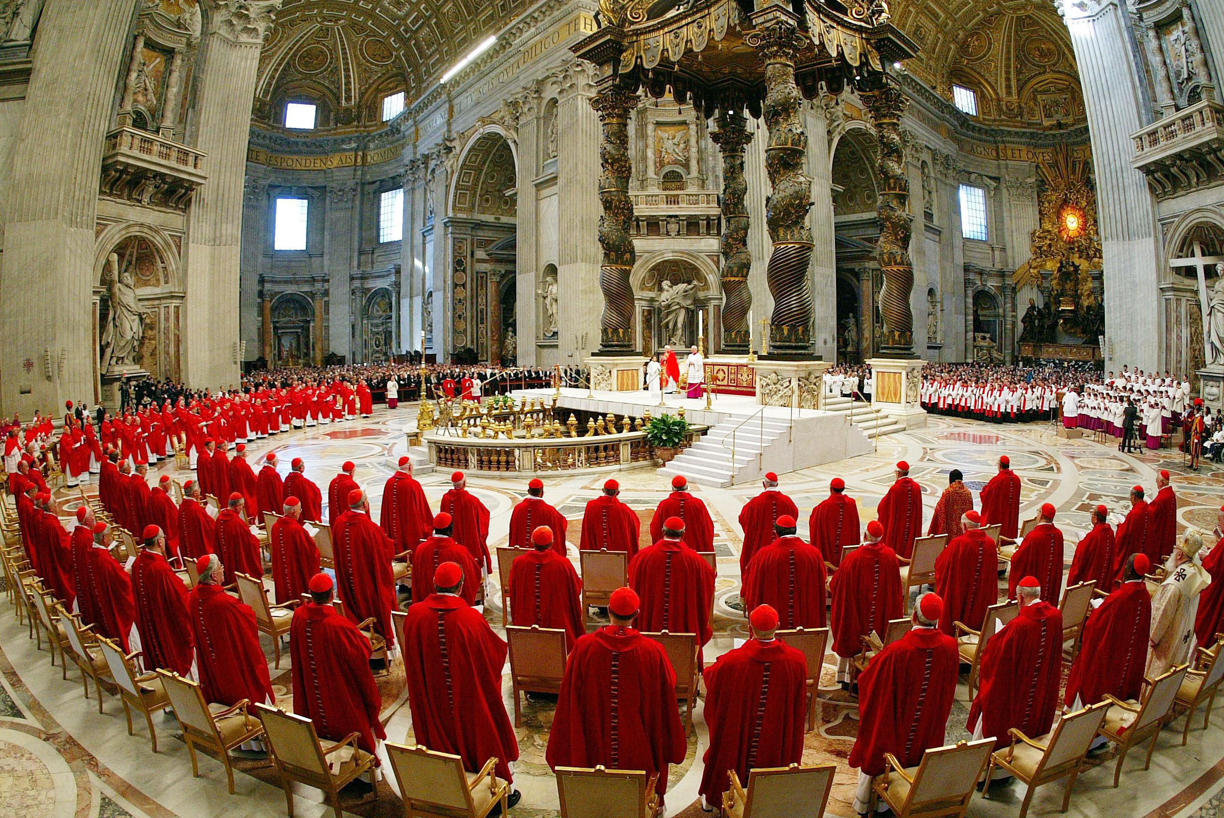 I cardinali vestiti con i paramenti rossi, in piedi davanti l'altare principale della Basilica di San Pietro per partecipare alla messa solenne ''pro eligendo pontifice'', che apre i riti del conclave per l'elezione del successore di Giovanni Paolo II il 18 aprile 2005.   ANSA