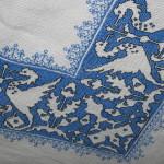 Particolare di una tovaglia a Punto Assisi con i classici motivi zoomorfi su sfondo blu