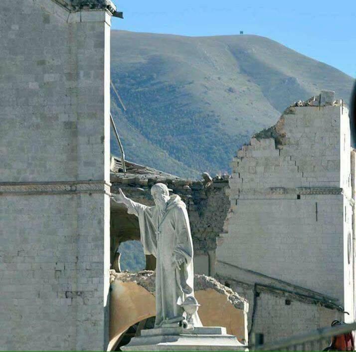 La statua di San Benedetto tra le rovine del terremoto del 30 ottobre 2016 a Norcia (Perugia)