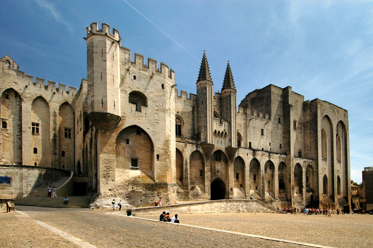 Avignon, France - June 16, 2005: Facade of the Palace of the Popes (Palais des Papes) in France. In front of the photo is a square with almost no people. Some persons are sitting on a somewhat higher part of the square.